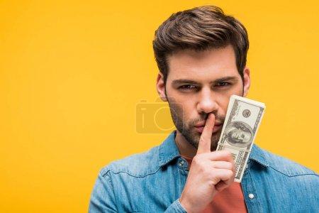 Photo pour Bel homme faisant le geste de silence et retenant des billets de banque de dollar d'isolement sur le jaune - image libre de droit