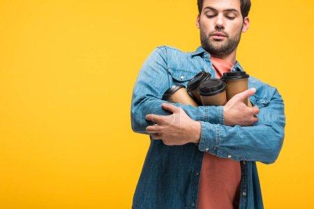 Photo pour L'homme beau retenant des tasses en papier avec le café pour aller isolé sur le jaune - image libre de droit