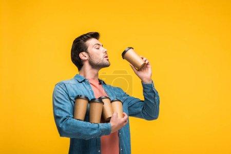 Photo pour Bel homme retenant des tasses en papier avec le café pour aller isolé sur le jaune - image libre de droit