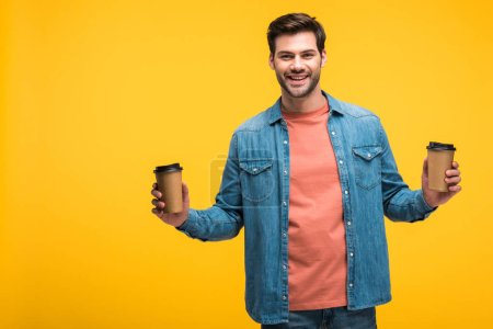 Photo for Handsome smiling man holding paper cups with coffee to go isolated on yellow - Royalty Free Image