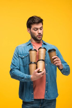 Photo for Handsome man holding paper cups with coffee to go isolated on yellow - Royalty Free Image