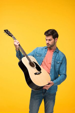 Photo for Handsome man holding acoustic guitar isolated on yellow - Royalty Free Image