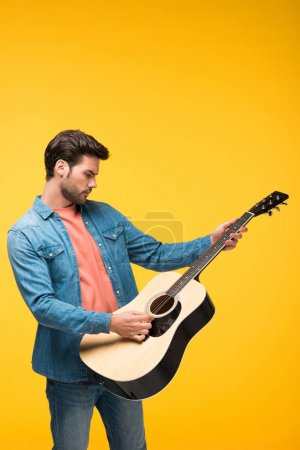 Photo for Handsome man playing acoustic guitar On yellow - Royalty Free Image