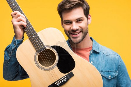 Photo for Handsome happy man holding acoustic guitar isolated on yellow - Royalty Free Image