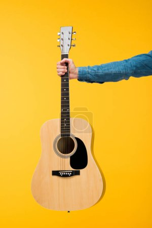 Photo for Cropped view of man holding acoustic guitar isolated on yellow - Royalty Free Image