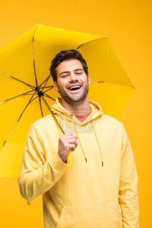 Photo pour Bel homme tenant parapluie et riant isolé sur jaune - image libre de droit