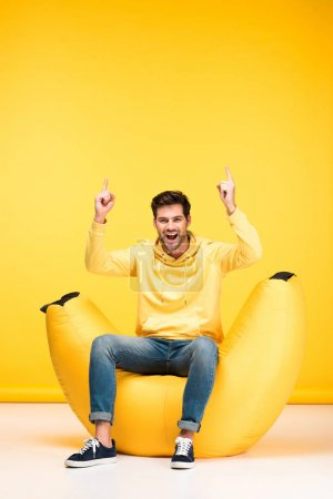 Photo for Excited man on bean bag chair pointing with fingers on yellow - Royalty Free Image