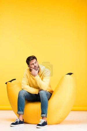 Foto de Hombre pensativo en la silla de bolsa de frijoles tocando la barbilla en amarillo - Imagen libre de derechos
