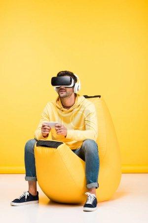Photo pour Homme sur haricot chaise sac avec smartphone en réalité virtuelle casque sur jaune - image libre de droit