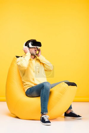 Photo for Excited man on bean bag chair in virtual reality headset on yellow - Royalty Free Image