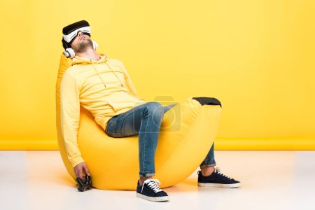 Photo for KYIV, UKRAINE - APRIL 12: man on bean bag chair with joystick in virtual reality headset on yellow - Royalty Free Image