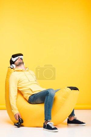 Photo pour KYIV, UKRAINE - 12 AVRIL : homme sur une chaise de sac de haricot avec joystick en réalité virtuelle casque sur jaune - image libre de droit