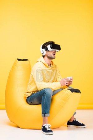 Photo pour Excité homme sur haricot sac chaise avec smartphone en réalité virtuelle casque sur jaune - image libre de droit