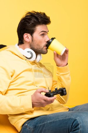 Photo for KYIV, UKRAINE - APRIL 12: man drinking coffee to go and playing Video Game isolated on yellow - Royalty Free Image