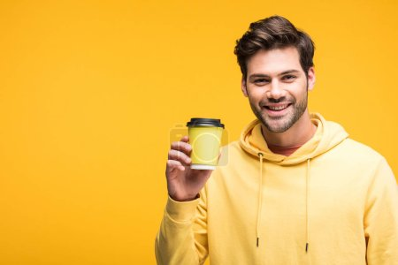 Photo for Handsome man in hoodie holding coffee to go isolated on yellow - Royalty Free Image