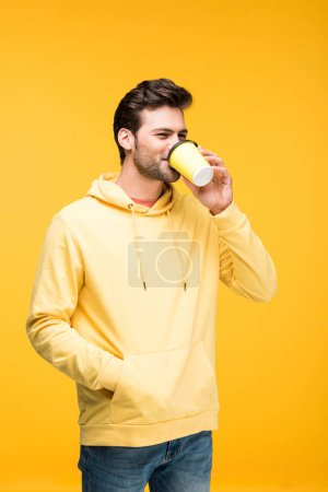 Photo for Handsome man in hoodie drinking coffee to go isolated on yellow - Royalty Free Image