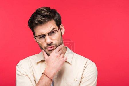Photo pour Beau homme pensif touchant le menton d'isolement sur le rose - image libre de droit
