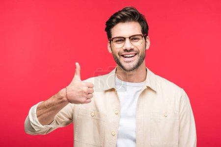 Photo pour Bel homme souriant montrant pouce isolé sur rose - image libre de droit