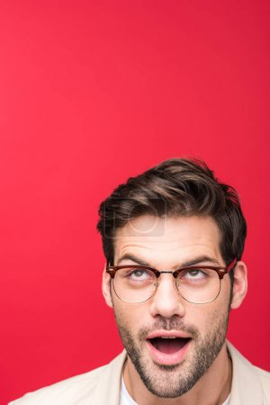 shocked handsome man in glasses looking up Isolated On pink