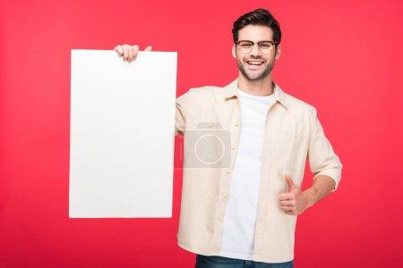 Photo pour Beau homme retenant le conseil vide et faisant le pouce vers le haut signedal'isolement sur le rose - image libre de droit