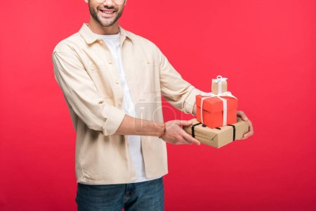 Cropped view of smiling man holding presents On pink