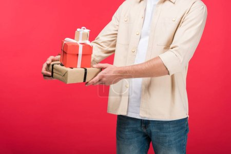 Photo for Cropped view of man holding presents On pink - Royalty Free Image