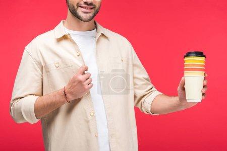 Photo pour Vue recadrée de l'homme retenant des tasses en papier avec le café pour aller isolé sur le rose - image libre de droit