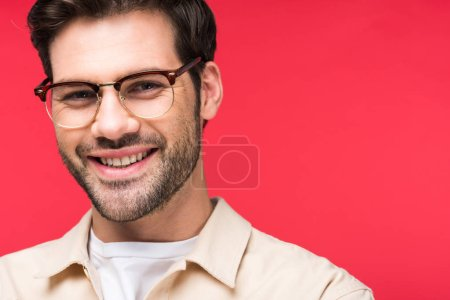 Foto de Smiling handsome man in glasses looking at camera Isolated On pink - Imagen libre de derechos