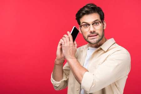Photo for Confused man talking on smartphone and looking at camera Isolated On pink - Royalty Free Image