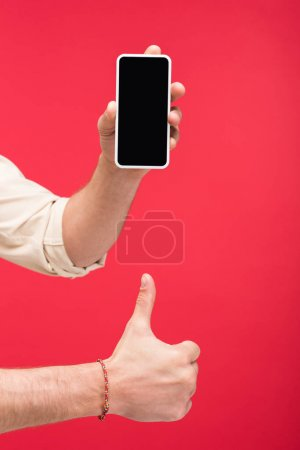 Photo for Cropped view of man holding smartphone with blank screen and doing thumb up sign Isolated On pink - Royalty Free Image