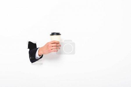 Foto de Vista recortada del hombre sosteniendo el café para ir desde el agujero en la pared en blanco - Imagen libre de derechos
