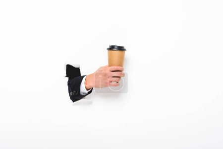 Photo for Cropped view of man holding coffee to go from hole in wall on white with copy space - Royalty Free Image