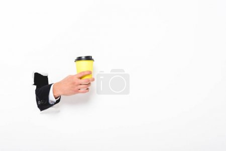 Photo for Partial view of man holding coffee to go from hole in wall on white with copy space - Royalty Free Image