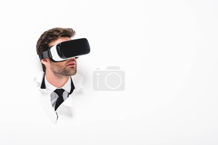 Photo for Man in Virtual reality headset behind hole in wall on white with copy space - Royalty Free Image