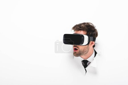 Photo for Shocked man in Virtual reality headset behind hole in wall on white - Royalty Free Image