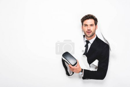 Photo pour Homme étonné retenant le casque virtuel de réalité derrière le trou dans le mur sur le blanc - image libre de droit