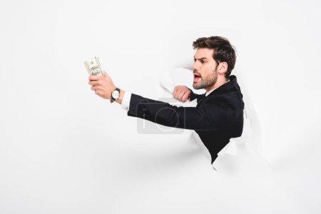 Photo pour Homme d'affaires fâché retenant des billets de banque de dollar derrière le trou dans le mur de papier sur le blanc - image libre de droit