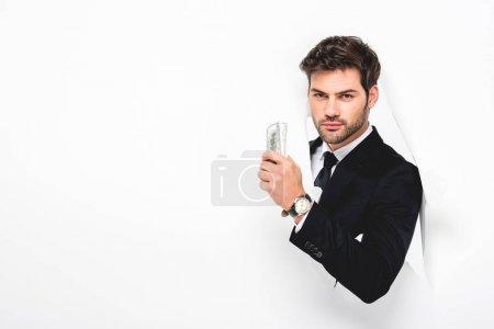 Photo pour Homme d'affaires beau retenant des billets de banque de dollar derrière le trou dans le mur de papier sur le blanc - image libre de droit