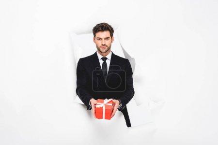 Photo pour Bel homme dans le procès avec le présent regardant l'appareil-photo par le trou dans le papier sur le blanc - image libre de droit