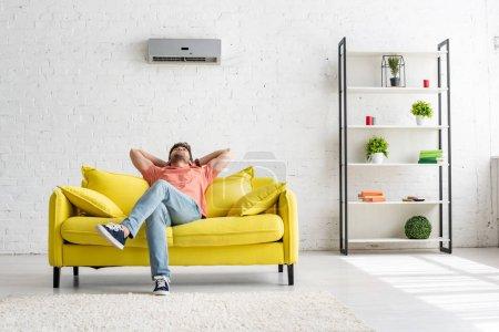 Foto de Joven hombre sentado en un sofá amarillo bajo el aire acondicionado en un apartamento espacioso. - Imagen libre de derechos