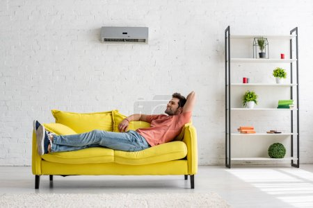Photo pour Bel homme souriant couché sur un canapé jaune sous climatiseur à la maison - image libre de droit