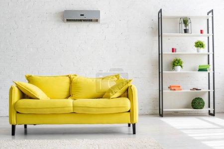 Photo for Spacious living room with air conditioner on white wall, yellow sofa and rack - Royalty Free Image