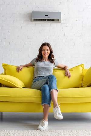 Photo pour Beautiful smiling woman sitting on yellow sofa under air conditioner at home - image libre de droit