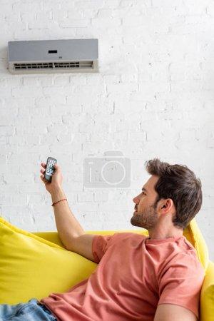 Photo pour Beau jeune homme retenant la télécommande tout en se trouvant sur le sofa sous le climatiseur - image libre de droit
