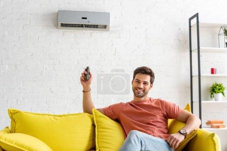 Photo pour Bel homme regardant l'appareil-photo tout en s'asseyant sous le climatiseur et en retenant la télécommande - image libre de droit
