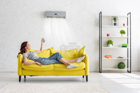 Photo for Attractive young girl lying on yellow sofa under air conditioner at home - Royalty Free Image