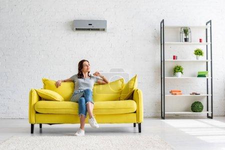 Photo pour Belle jeune femme assise sur canapé jaune sous climatiseur dans un appartement spacieux - image libre de droit
