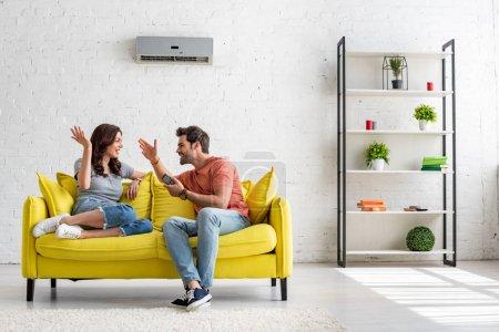 Photo pour Homme et femme gai parlant tout en s'asseyant sur le sofa jaune sous le conditionneur d'air - image libre de droit