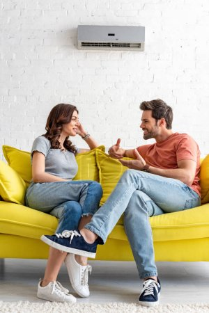 Photo for Smiling man and woman sitting on yellow sofa under air conditioner at home - Royalty Free Image