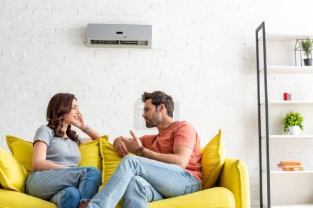 Photo for Cheerful man and woman talking while sitting on yellow sofa under air conditioner at home - Royalty Free Image